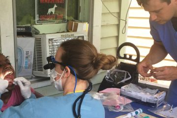 student dentists examine child at home