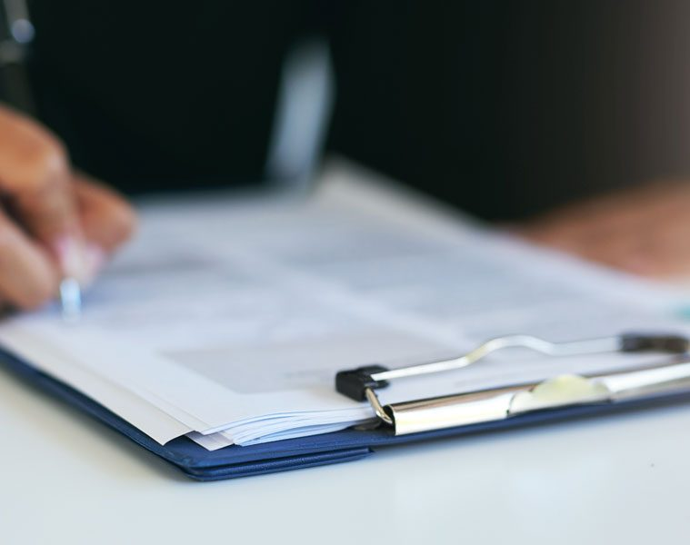 image of a person's hand filling out an insurance claim