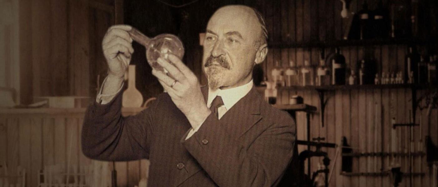 Photo of Leo Baekeland holding object in lab