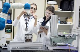 Two female engineers in a lab working on a robotic arm