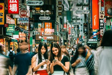 Two women looking at their phones in the center of a crowded area surrounded by advertisements and blurred people