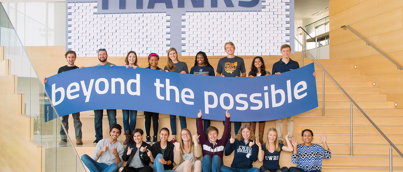 "Students hold a banner that says ""beyond the possible"" with a sign behind them that says ""thanks"""