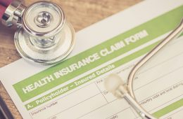 a health insurance claim form with a stethoscope on top