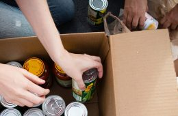 people putting canned food in a box