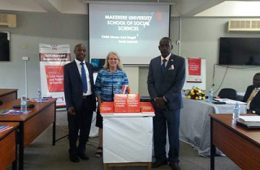 Photo of David Kaawa-Mafigiri, Jill Korbin and Eddy Walakira with table with books on it