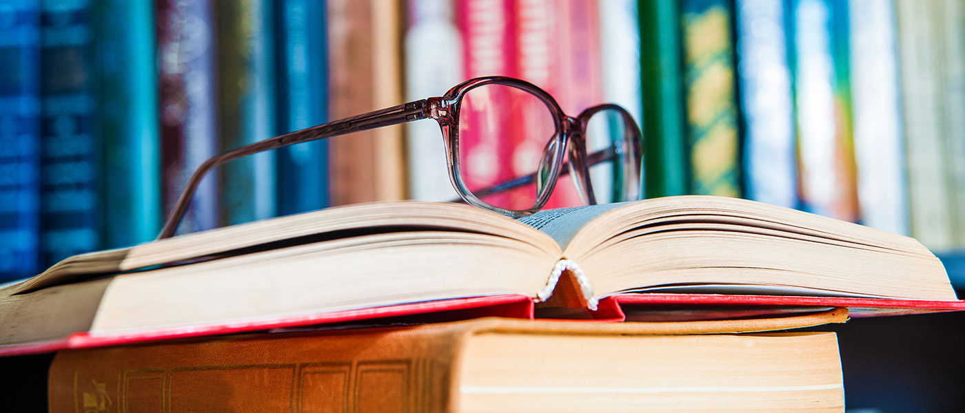 Glasses sitting on open book with more books in the background