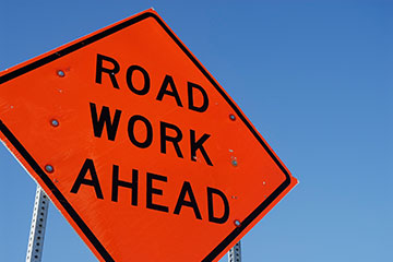 "Sign that says ""Road Work Ahead"" against blue sky background"