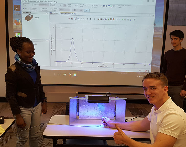 Students demonstrate phototherapy device they developed to Uche Anene-Nzelu