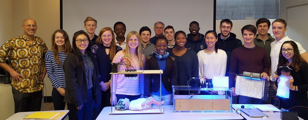 Group photo of SAGES class students with Uche Anene-Nzelu and Dan Lacks with student phototherapy device prototypes