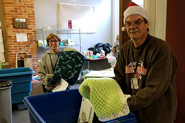 Two individuals prepare items made by Crafters@Case to be donated
