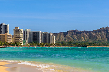 Photo of a Waikiki Beach with buildings and mountain in the background