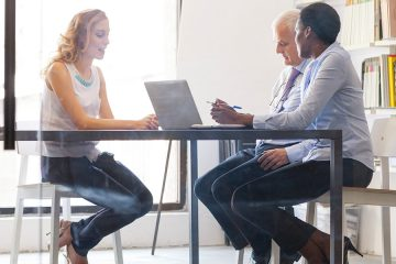 Photo of a young woman at table for interview with man and woman