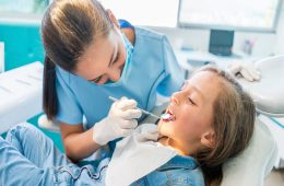 Beautiful girl at the dentist getting a check up on her teeth - pediatrics dental care concepts