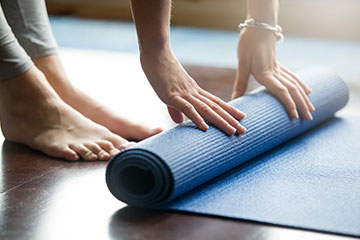Close-up photo of a woman unrolling a yoga mat