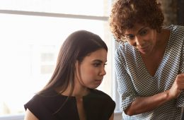 Photo of a businesswoman helping another woman at work