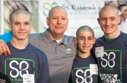 Four people pose for photo with shaved heads at previous Shave It Off event