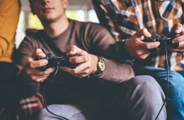 People playing video games, with controller in hands