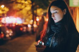 Young woman texting while standing on sidewalk at night
