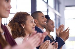 Image of staff members standing in a line clapping