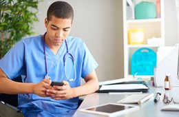A doctor in scrubs sitting at desk and looking at phone