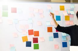 Photo of person looking at post-it notes on white board