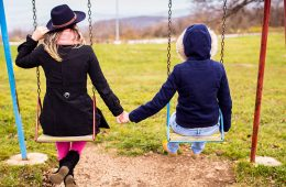 Two young women holding hands while on swings