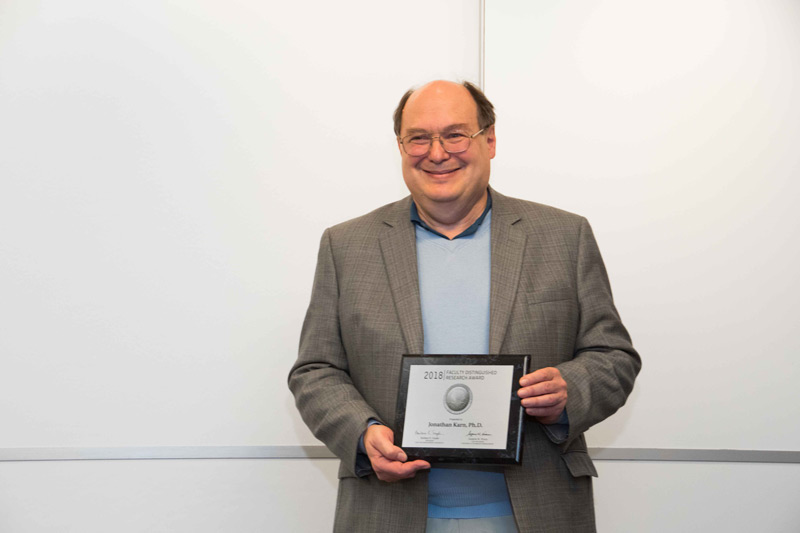 Photo of Jonathan Karn holding Faculty Distinguished Research Award plaque