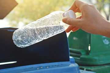 Photo of hand putting bottle in recycling bin
