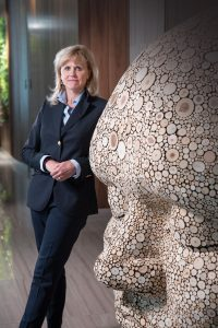 Case Western Reserve University alumna Ann McKee next to a statue of a head