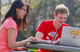Two students sitting at a picnic table working on laptops