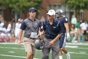 High Marshall carrying a football helmet at a CWRU football game