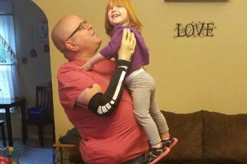 Keith Vonderhuegel lifts his granddaughter
