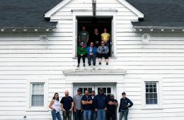 Case Western Reserve University Farm staff and researchers pose for photo with some in front of main barn and others in a loft window area above