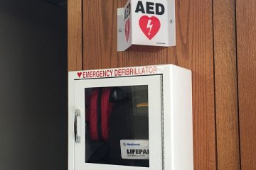 "Photo of cabinet on wall that has AED and Stop the Bleed kits with a triangular sign above that says ""AED"""