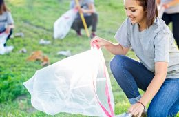 A woman picks up litter in a park