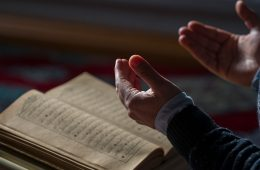 man praying over religious text