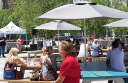 People sitting around at picnic tables during an Uptown event