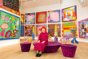 Yayoi Kusama sitting in gallery surrounded by her artwork