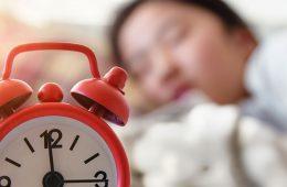 Sleeping teenage girl with alarm clock in front of her