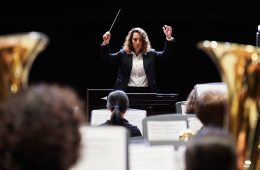 A woman conducts musicians