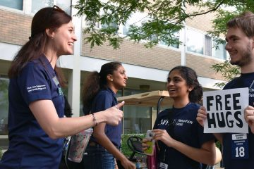 """Natalie Nielsen talks to fellow Case Western Reserve University orientation leaders, while one male student holds sign that says """"Free Hugs"""""""