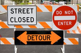 """Traffic signs on street barrier that say """"street closed,"""" """"do not enter"""" and """"detour"""""""