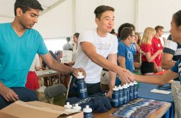 Male and female Case Western Reserve University students shake hands at a student organization information fair booth