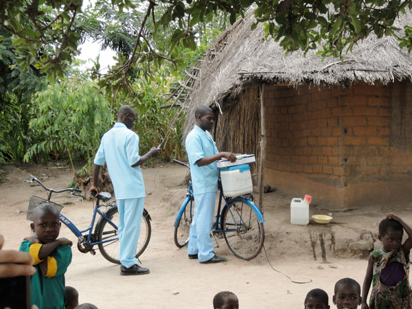 Health care workers in Malawi bike to villages to give vaccinations