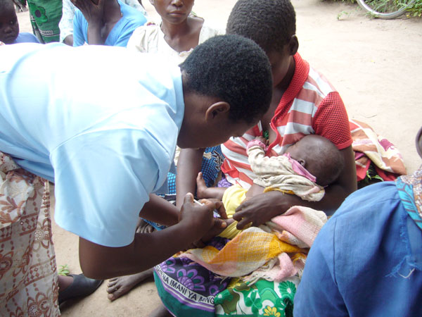 Malawi health care worker gives infant vaccination