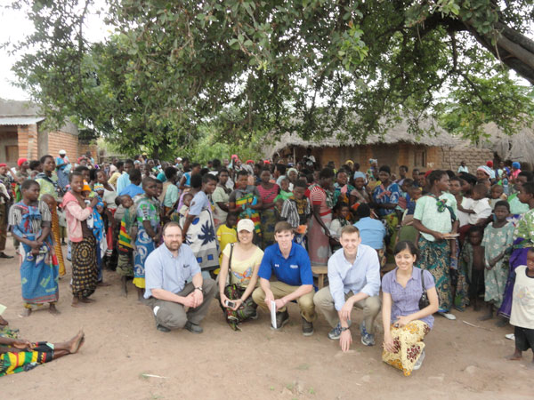 CWRU students and professor stand with residents in Malawi
