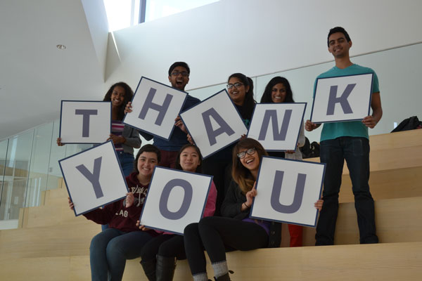 """CWRU students hold signs spelling """"thank you"""" on steps at the Tink"""
