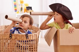 Two boys pretending to be pirates in boxes and baskets