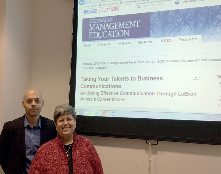 Alperen Manisaligil and Diana Bilimoria stand near a projection of their research paper