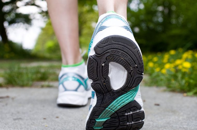 Rear view of woman's shoes as she walks on path